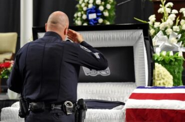 Police Officer Saluting Casket