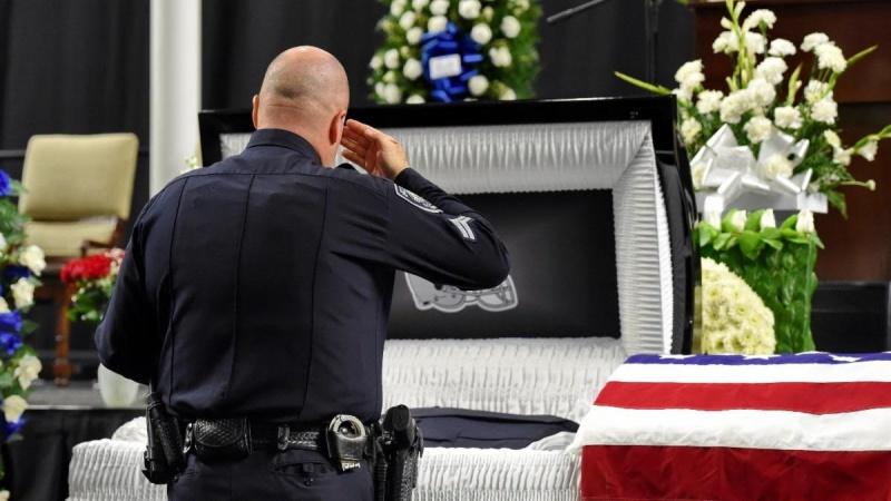Police Officer Saluting Casket
